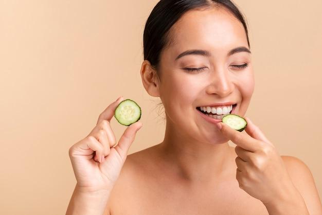 Close-up brunette woman biting cucumber slice