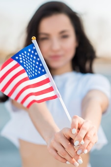 Close-up brunette woman holding usa flag in hands