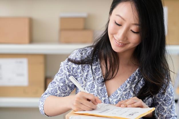 Primo piano su bruna giovane donna che scrive una nota di pacco