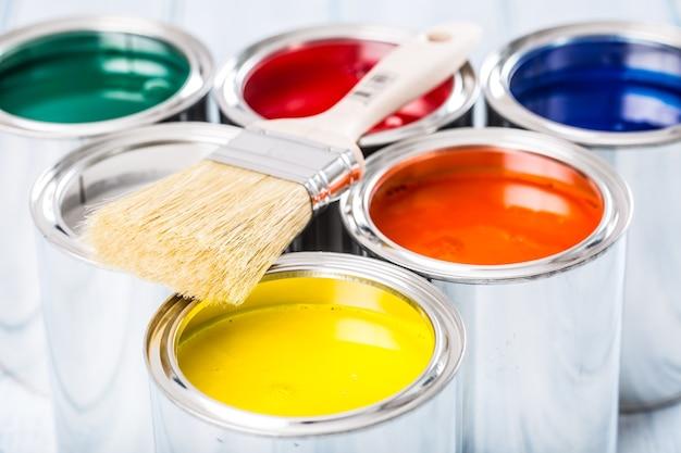 여러 가지 빛깔된 페인트 캔에 누워 클로즈업 브러시입니다.