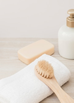 Close-up of brush; towel; soap and cosmetic bottle on wooden surface