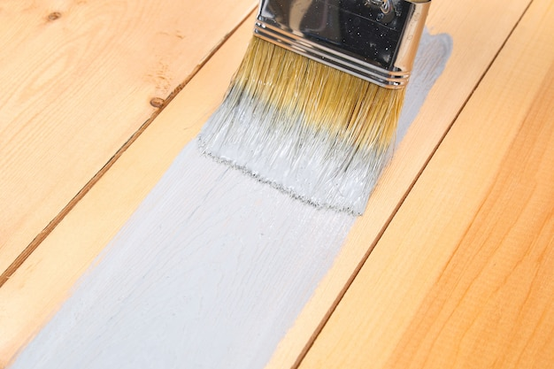 Close up brush with white paint for wooden planks