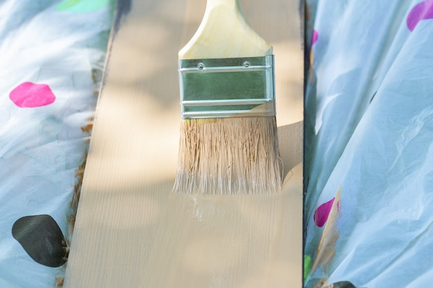 Close-up brush in yellow paint , which is painted a wooden board. horizontal photography