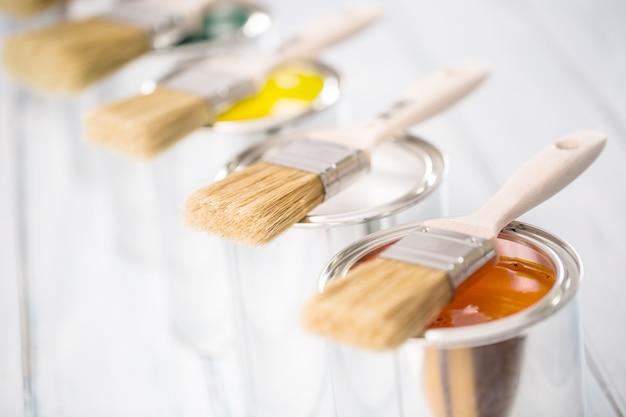 여러 가지 빛깔된 페인트 캔에 누워 클로즈업 브러쉬입니다.