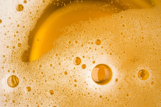 Close up bubble froth of beer in glass or mug for background on top view