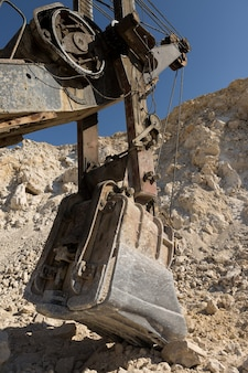 A close-up of the bucket of a heavy large excavator in a quarry.