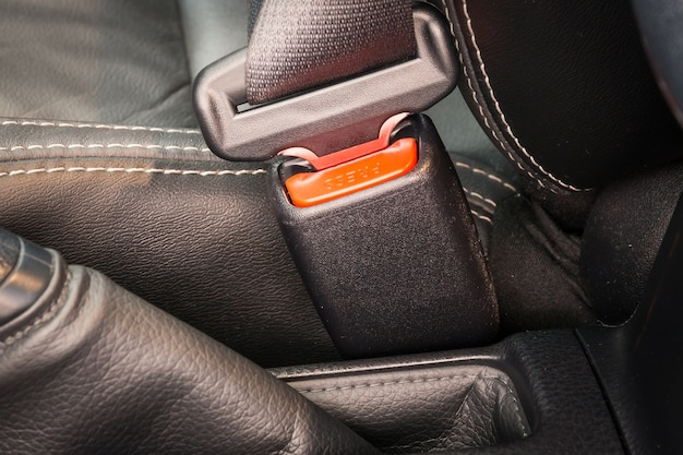 Close-up of the buckle of a seat belt or safety belt for driving and transportation by car.
