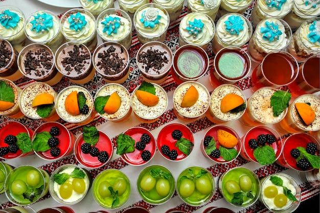 新鮮なフルーツのゼリーとクリームのクローズアップビュッフェテーブル。デザート付きのウェディングビュッフェ。
