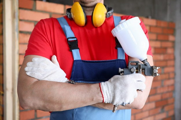 Close-up of a builder holding spray gun in his hands. painting technology tool.