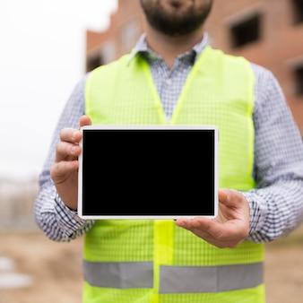 Close-up builder man holding tablet