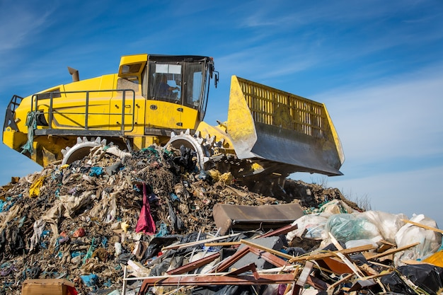 Close up of a bulldozer on the huge household landfill or dump waste, environmental or ecology problem
