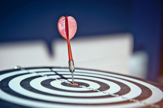 Close-up the bullseye has dart arrow hitting the center.