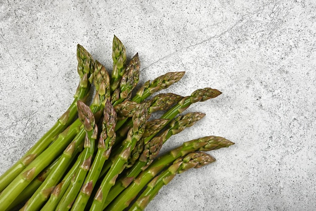 Close up bunch of fresh green asparagus on cutting board or grey stone table surface, elevated top view, directly above