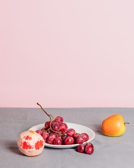 Close-up of a bunch of grapes, a peeled grapefruit and an apple on a pink background. minimalist still life with copy space for your text.
