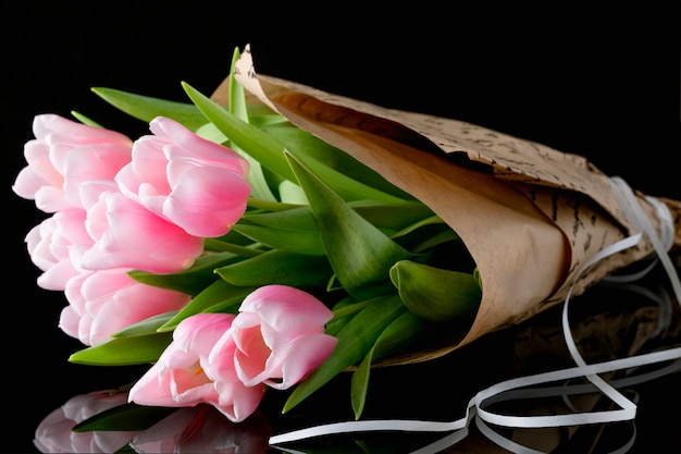 A close up of a bunch of pink tulips against a black