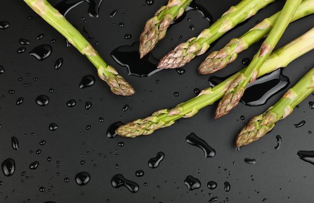 Close up bunch of washed fresh green asparagus on black table with drops of water, elevated top view, directly above