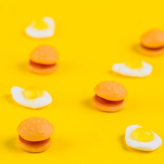 Close-up of burger candies and fried egg gummies on yellow background