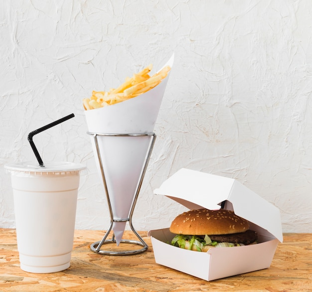 Close-up of burger; french fries and disposal cup on wooden desk
