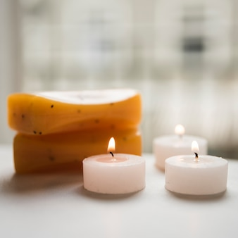 Close-up of burning candles and soaps in spa