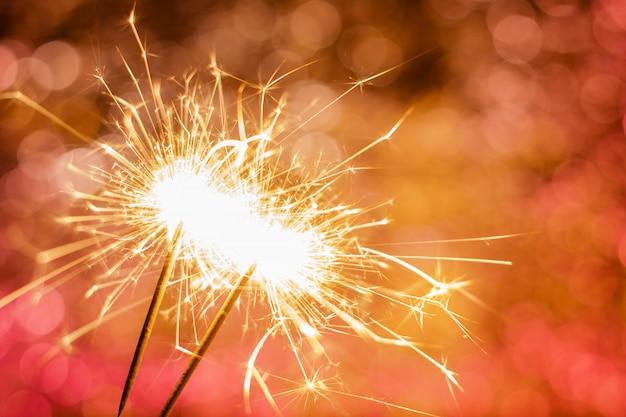 Close up of burning sparklers on beautiful bokeh background