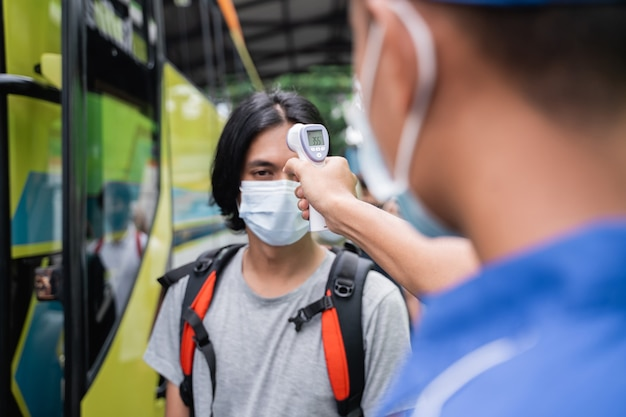 Close up of a bus crew in blue uniforms and a hat using a thermo gun inspects the male passenger in the mask before boarding the bus