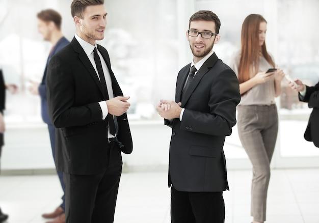 Крупным планом. коллеги по бизнесу обсуждают проблемы бизнеса, стоя в офисе