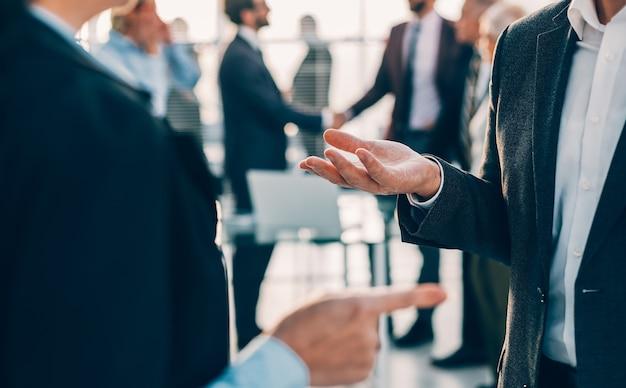 Закройте вверх. коллеги по бизнесу обсуждают текущие задачи стоя в офисе. бизнес-концепция