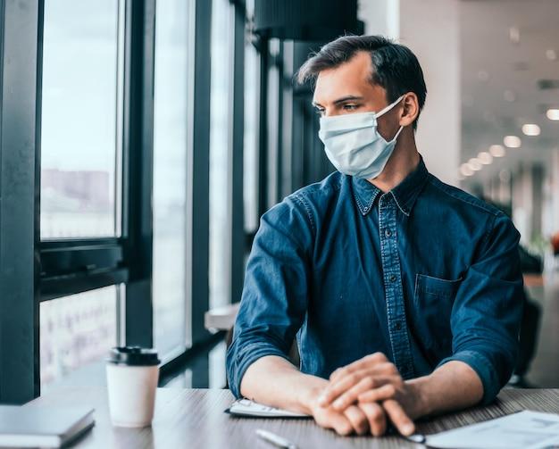 閉じる。財務書類を扱う保護マスクの同僚。