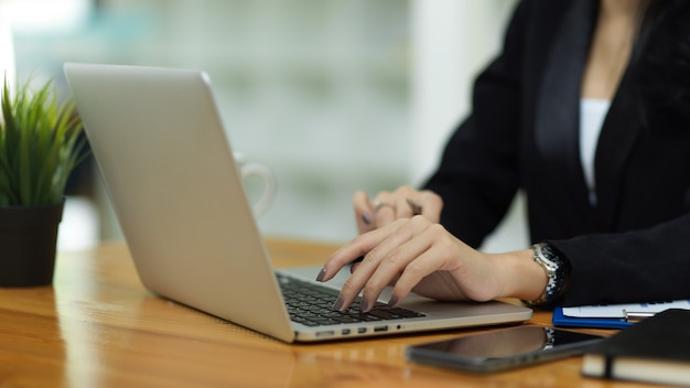 Close up business female in black suit hands typing on laptop keyboard on work space
