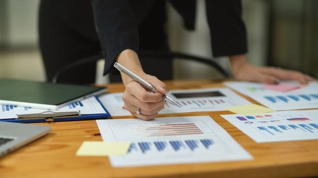 オフィス、財務管理のテーブルに文書に署名するビジネスの女性の手をクローズアップ