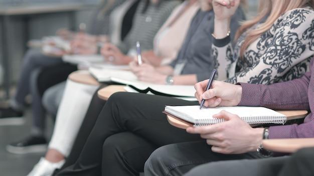 クローズアップ。会議室に座っているクリップボードでメモを取るビジネスグループ。