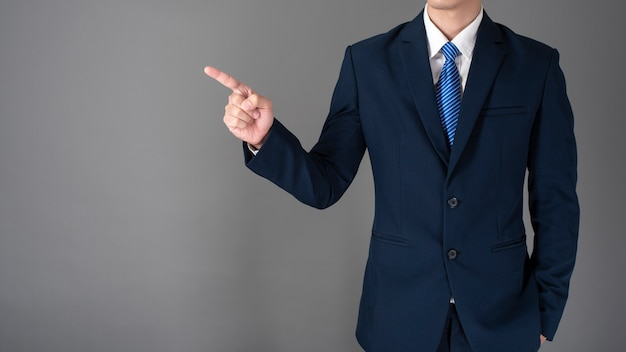 Close up of business man in blue suit is pointing something on gray background