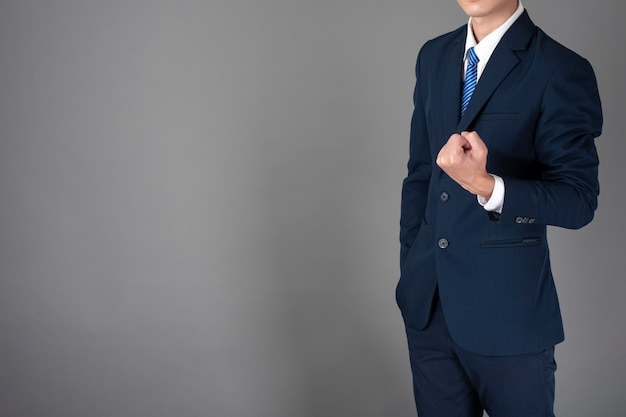 Close up of business man in blue suit is successful  in grey background