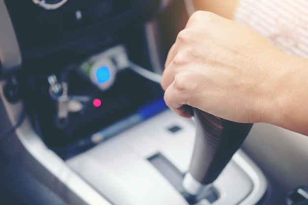 Close up business man driver hand shifting the gear stick