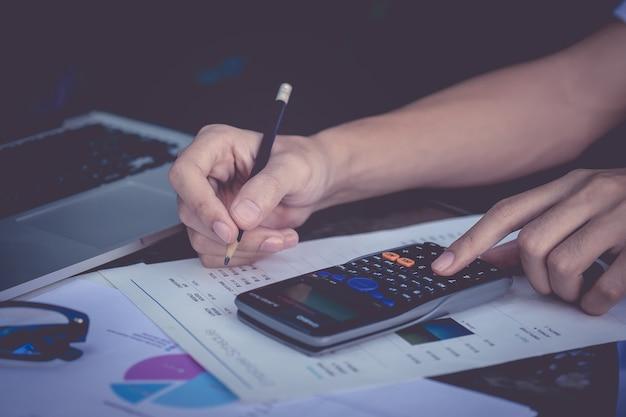 비즈니스 사람 손을 잡고 스마트 폰 및 금융 하 고 집 사무실에서 비용에 대 한 나무 테이블에 계산을 닫습니다. 회계사 개념.