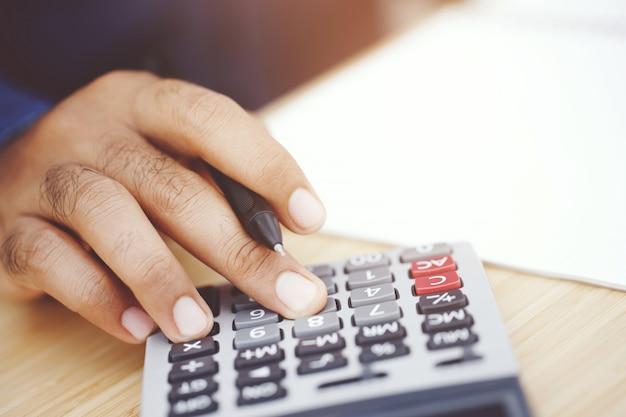 電卓を使用してビジネスの男の手を閉じます。貯蓄財政の概念。メモ帳