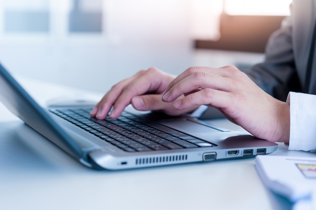 Close up of business man hands typing on laptop conputer