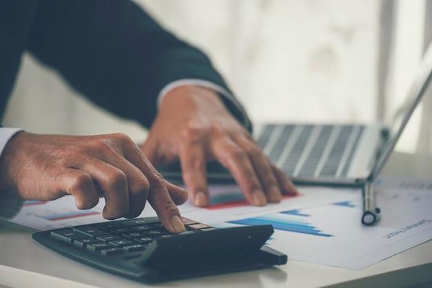 計算機を使用してビジネスマンの手をクローズアップ税財務法案税監査財務概念