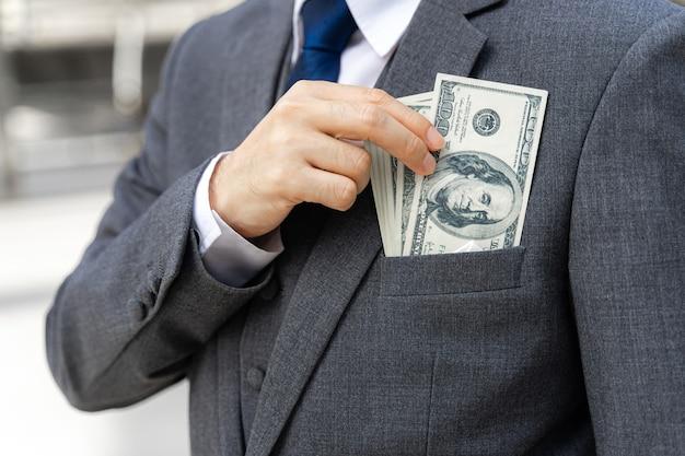 手にお金の米ドル札を持っているビジネスマンをクローズアップ