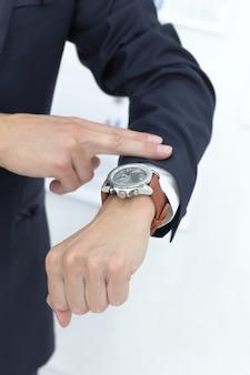 Закройте вверх. деловой человек, глядя на его наручные часы.