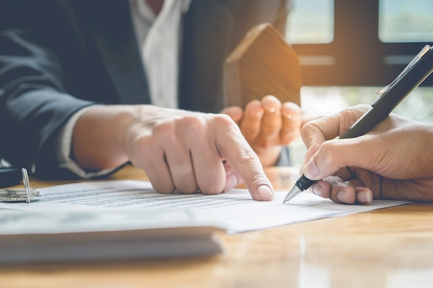 Close up of business man pointing and signing agreement for buying house. bank manager concept.