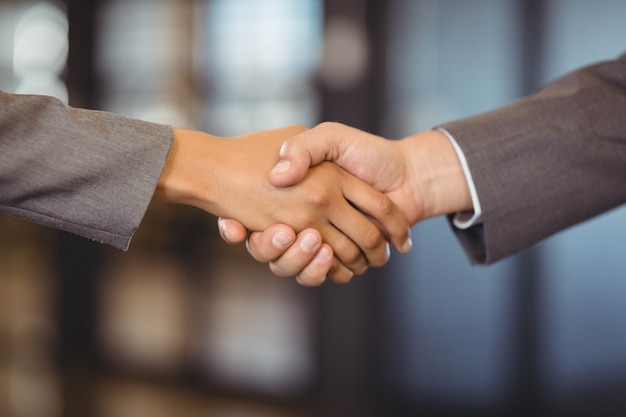 Close-up of business man shaking hands with business woman in office
