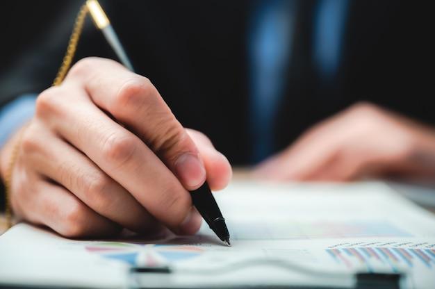 契約、古典的なビジネスの成功の概念を作る契約に署名するビジネスの男性を閉じる