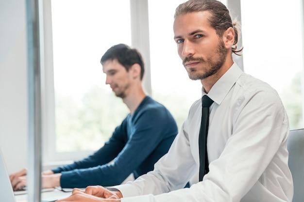 閉じる。オフィスの机に座っているビジネスマン。人とテクノロジー。