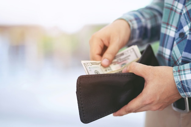 Close up business man standing  hand hold count the money spread of cash wallet. concept finance saving money.