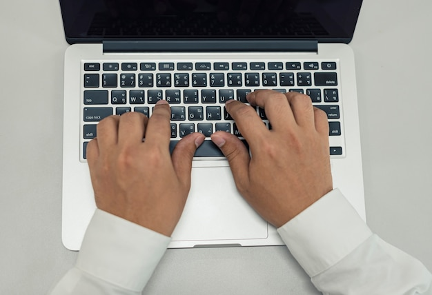 Close up business man typing on laptop on desk, home office