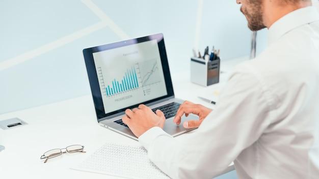 확대. 재무 데이터를 분석하기 위해 노트북을 사용하는 비즈니스 사람.