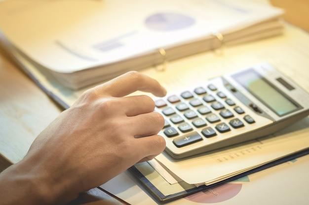 재무 용지, 세금, 회계, 회계사 개념으로 계산하기 위해 계산기와 노트북 컴퓨터를 사용하여 비즈니스 사람을 닫습니다.