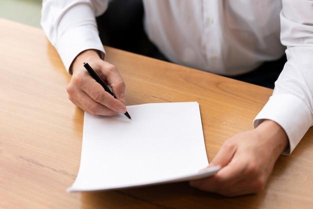 Chiuda sull'uomo di affari che usando la penna