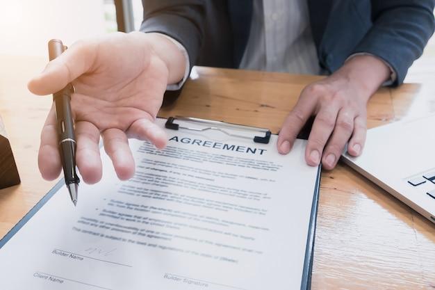 署名している契約を待っているビジネスマンを閉じます。